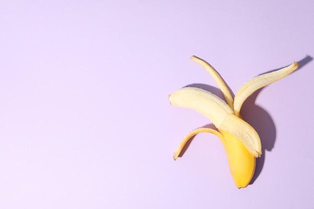 Раскрытый банан на фиолетовом столе. свежие фрукты