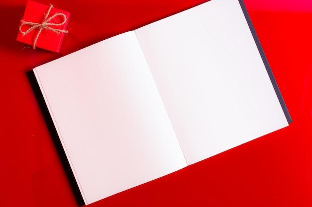 赤い背景の上のギフトボックスと空白の雑誌を開く