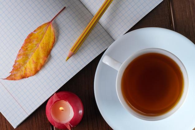 갈색 나무 배경에 뜨거운 차 한 잔 옆에 연필이 있는 체크 무늬 시트가 있는 빈 공책을 열었습니다.