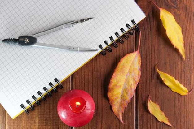 갈색 나무 배경에 나침반이 있는 체크 무늬 시트가 있는 빈 노트북을 열었습니다.