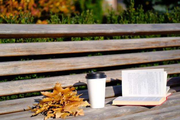 Открытая книга и чашка кофе на деревянной скамейке в парке