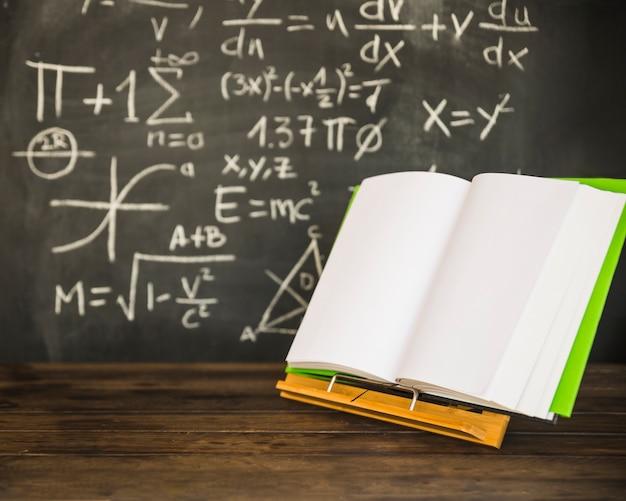 Opened book on book holder near blackboard