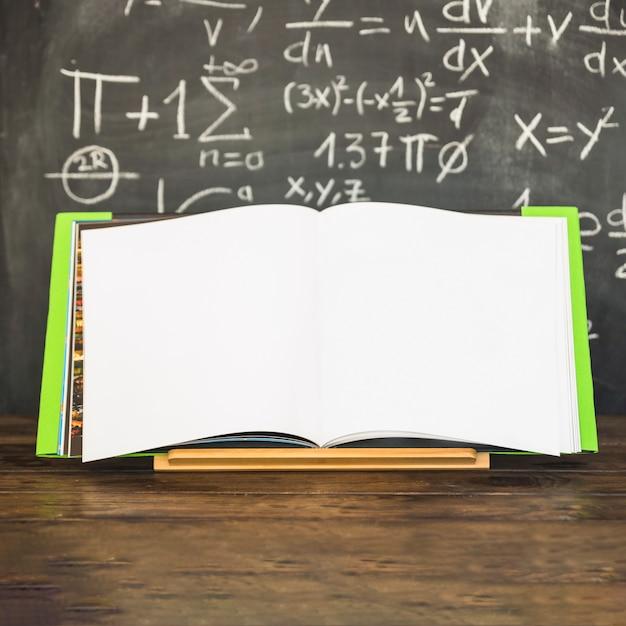Opened book in book holder near chalkboard