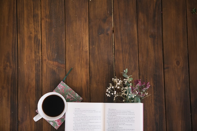 Opened book and coffee with bouquet