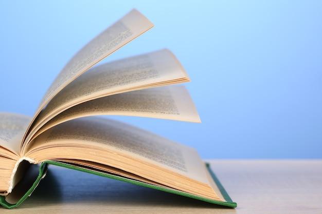 Открытая книга на деревянном столе на цветной стене