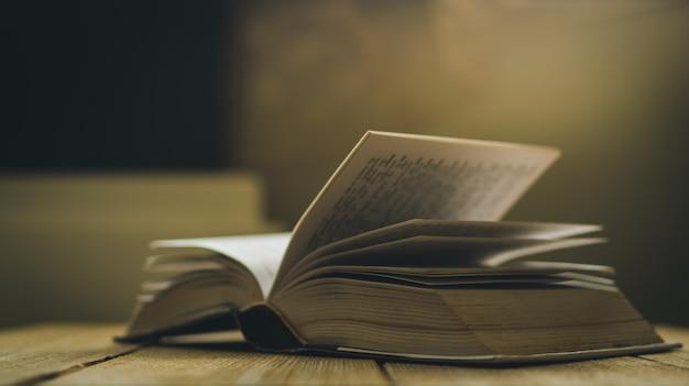 나무 테이블, 필드 및 영화관 색상 효과의 얕은 깊이에 열린 책