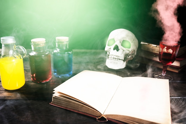 Opened book and skull with glowing eyes on table