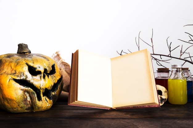 Opened book and spooky pumpkin on table