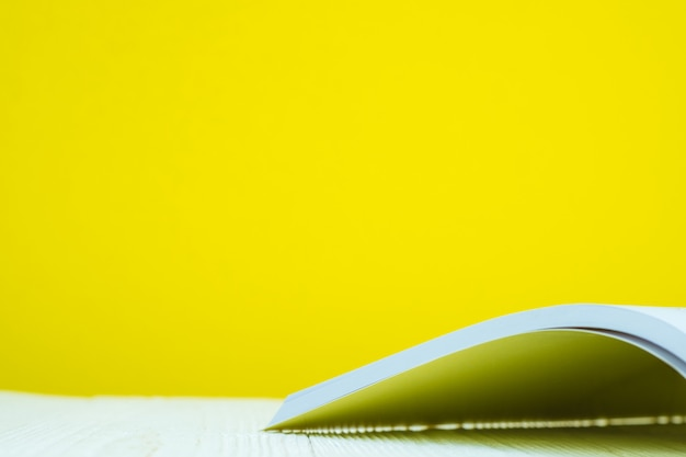 Opened book on white table with yellow background.