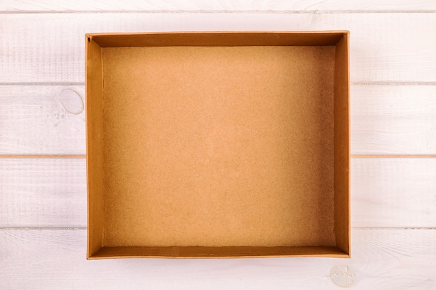 Opened brown blank cardboard box on wooden , vintage, toned top view