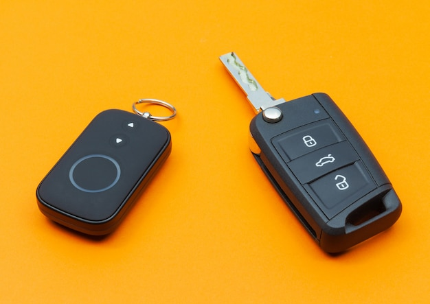Opened car key with remote control on an orange background
