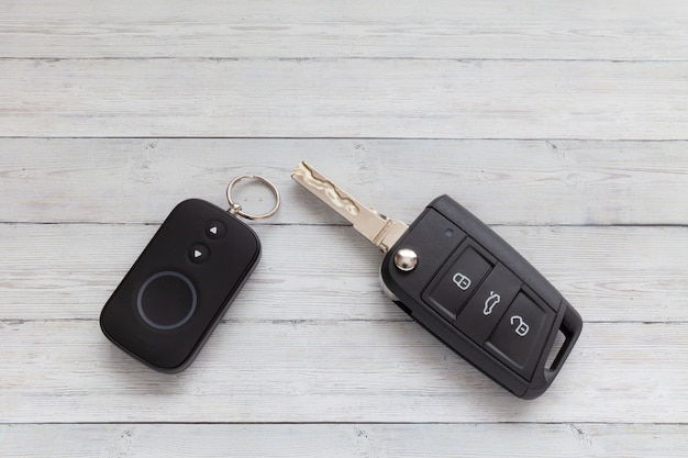 Opened car key with remote control on wooden background