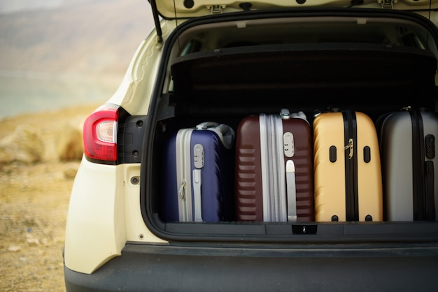 Opened car trunk full of suitcases, luggage, baggage.