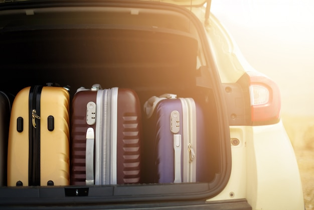Opened car trunk full of suitcases in sunlight effect.