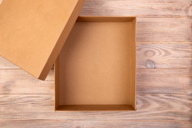 Opened cardboard box on a wooden table. top view