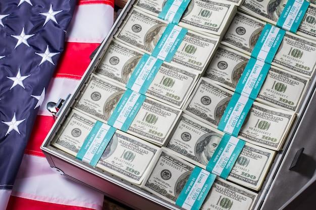Открытый футляр с долларовыми пачками. флаг сша, чемодан и деньги. банк растет. риск того стоит.