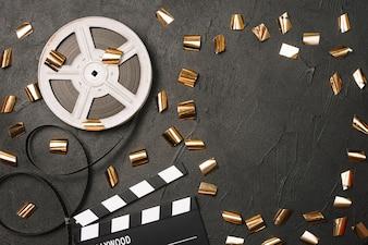Opened clapperboard and film bobbin under confetti