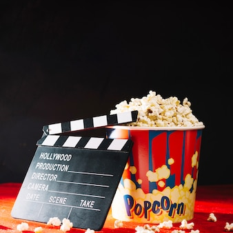 Opened clapperboard leaning against popcorn bucket