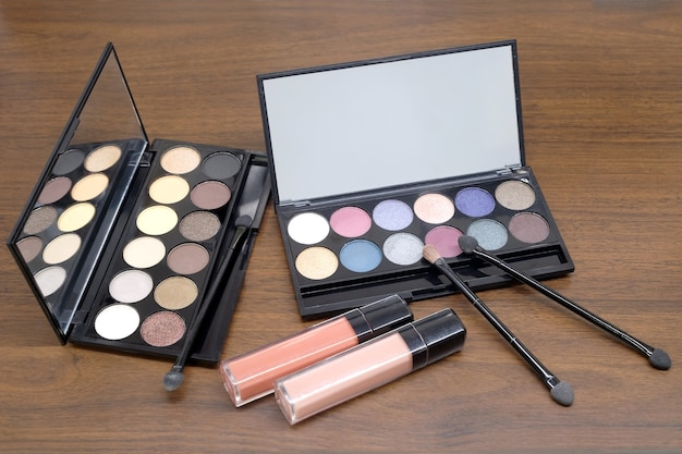 Opened cosmetic set with round colorful eye shadows and brushes in black plastic case with mirror and two pink lipstick tubes on wooden background closeup
