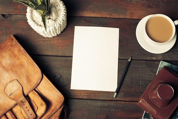 クラフトペーパー封筒、紅葉、木製のテーブルの上のコーヒーを開く