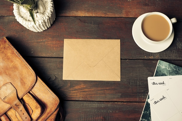 Opened craft paper envelope, autumn leaves and coffee on wooden table