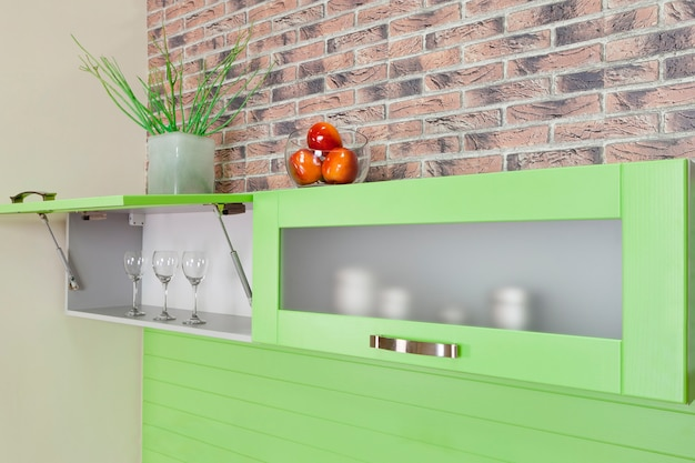 緑のキッチンの中に台所用品が入った戸棚を開けた