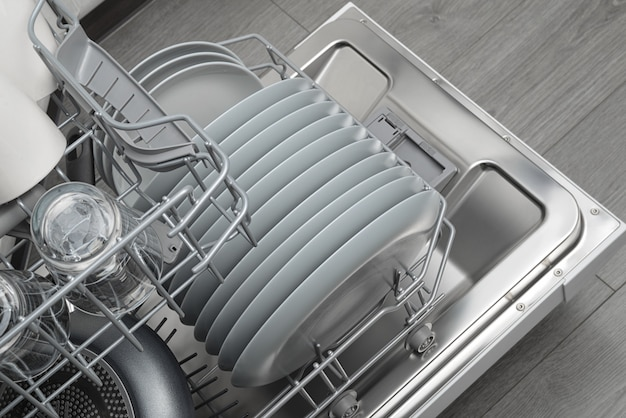 Opened domestic dishwasher with cleaned dishware