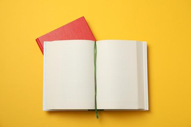 Раскрытая пустая книга и красная книга на желтом космосе, месте для текста
