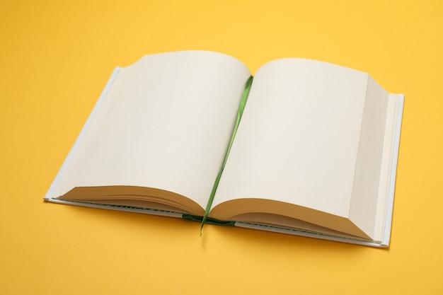 Открыта пустая книга на желтом пространстве, место для текста