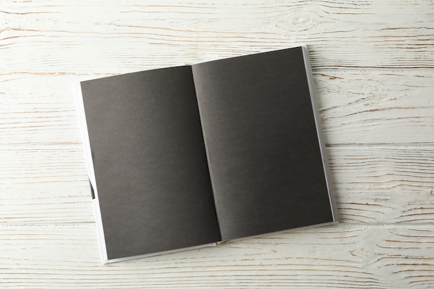 Opened empty book with black sheets on wooden space, space for text