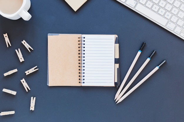 Opened empty notebook near stationery and keyboard