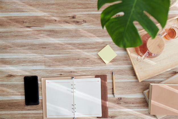 Открытый пустой планировщик, смартфон и поднос с чайником и чашкой на столе, вид сверху