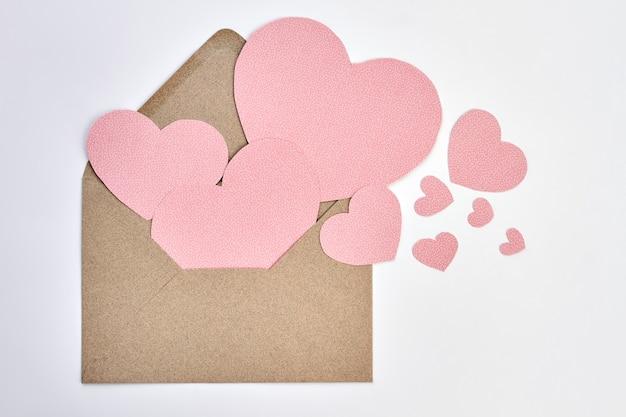 Открытый конверт и розовые бумажные сердца. конверт дня святого валентина из крафт-бумаги и декоративных сердечек на белом backgound. выразите свою любовь письмом.