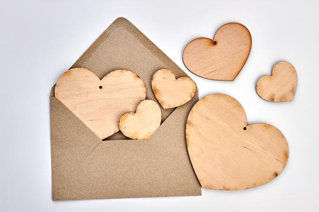 Открытый конверт и фанерные сердца. конверт в винтажном стиле и деревянные сердца на белом фоне. с днем святого валентина.