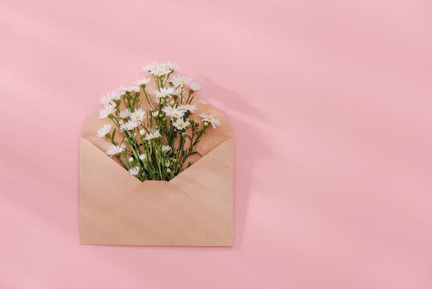 ピンクの背景、トップ ビューにフラワー アレンジメントで開いた封筒。お祝いの挨拶のコンセプト