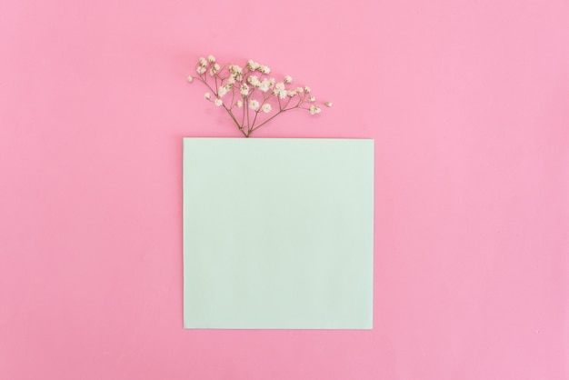 Opened envelope with peonies flowers arrangements on pink background, top view