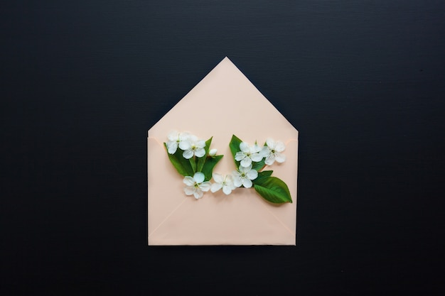 Opened envelope with spring flowers arrangements on black background