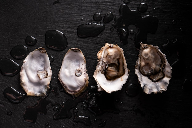 Opened fresh oysters on a dark background and water drops. rostik style.
