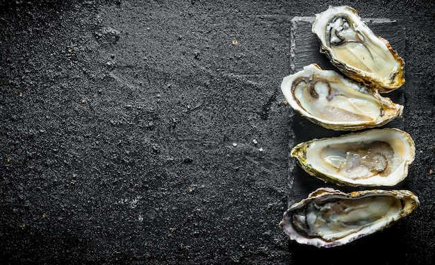 Opened fresh oysters on stone stand on black rustic table