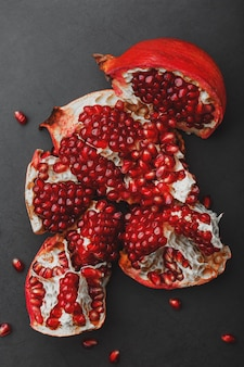The opened fruits of a ripe open pomegranate lie.