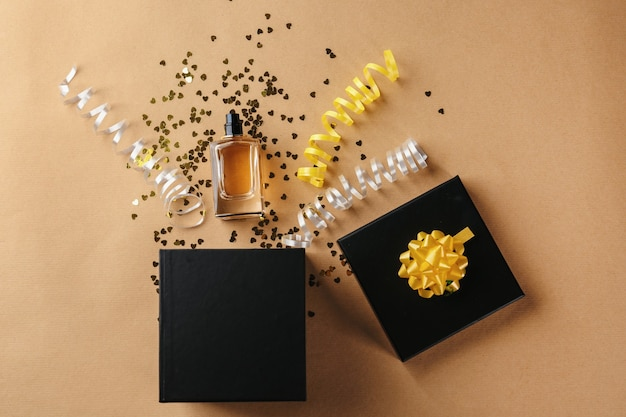 Opened gift box, perfume and decor on color background, top view