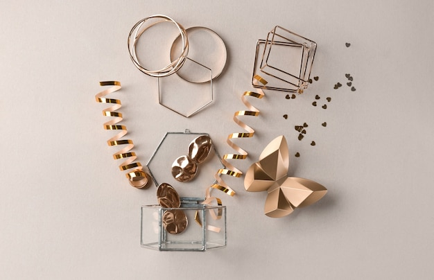 Opened glass box, golden accessories and decor on light background, top view
