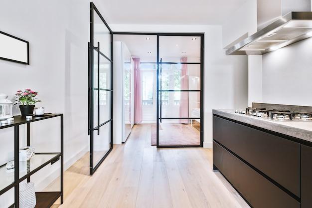 Открытая стеклянная дверь, ведущая в спальню из стильной кухни в современной светлой квартире