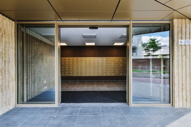 Opened glass door leaning into hall of modern apartment building on city street
