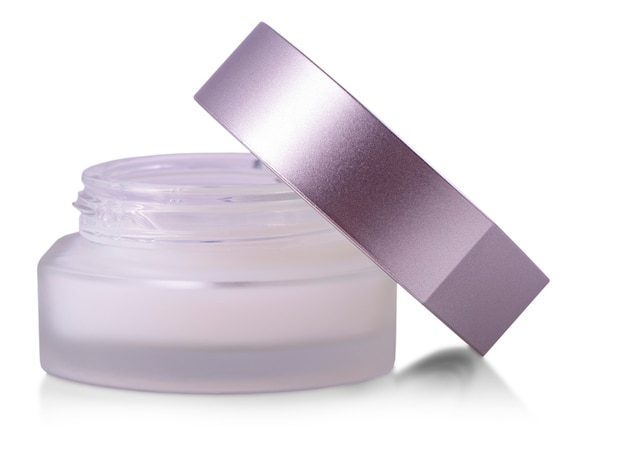 Opened glass jar of beauty cream with cap isolated on white