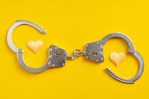 黄色の背景に開いた手錠