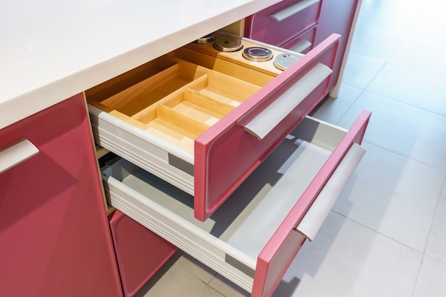 Opened kitchen drawer with plates inside, a smart solution for kitchen storage and organizing