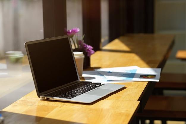 Открытый макет черного экрана ноутбука и оформление документов на деревянном столе