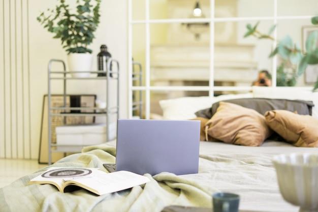 自宅のフリーランスのコンセプトから明るいスカンジナビアのインテリアワークでベッドの上にラップトップノートブックを開きました。高品質の写真