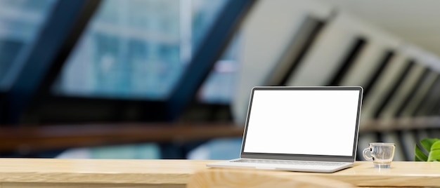 Opened laptop screen mockup copy space on wood table top blurred board room in the background